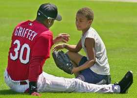 Cincinnati Reds centerfielder Ken Griffey Jr., shares a moment on the outfield grass with his son Trey Griffey, 10, before Monday's Grapefruit League game against the Tampa Bay Devil Rays in Sarasota, Fla., March 11, 2002.