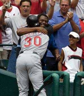 Cincinnati Reds Ken Griffey Jr. gets a big hug from his father Ken Griffey Sr., as his oldest son Trey watches, after hitting career home run number 500 in the sixth inning against the St. Louis Cardinals Sunday, June 20, 2004 at Busch Stadium in St. Louis.