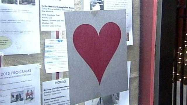 Each year, in the dark of night, he or she tapes paper hearts on store fronts in the downtown and Old Port areas.