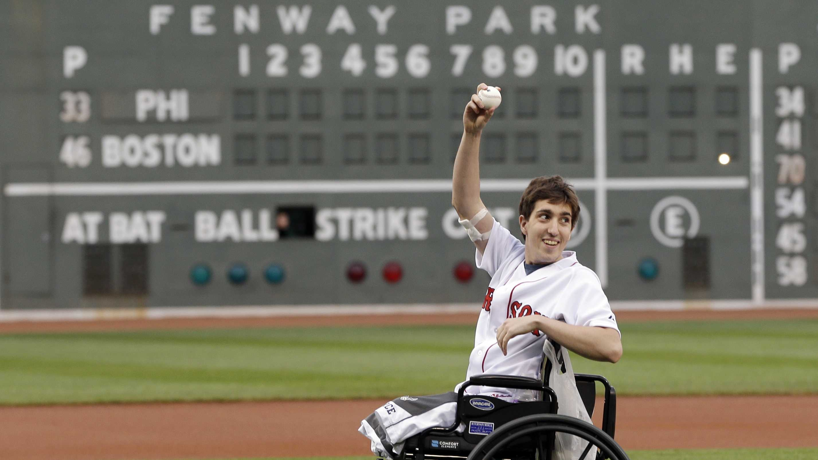 Boston Marathon bombing survivor Jeff Bauman acknowledges cheering fans before throwing out the ceremonial first pitch at Fenway Park prior to a baseball between the Boston Red Sox and the Philadelphia Phillies Tuesday, May 28, 2013, in Boston.