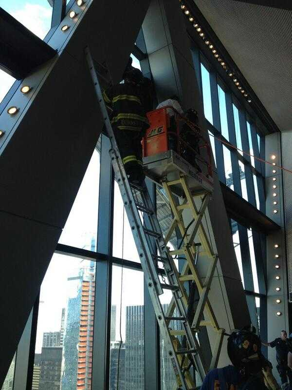 Workers attempt to cut a hole in the window to rescue the two workers. Shortly after 4 p.m., they were successful.