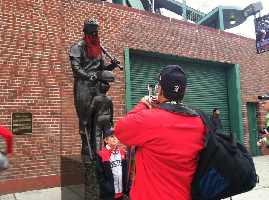 Fans take pictures of the bearded statues outside Fenway Park.