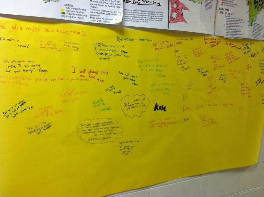 The students are writing notes to Kobe on a large piece of paper in the school's hallway.