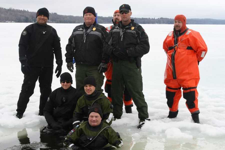 Members of the Maine Warden service dug a hole in the ice for the plungers and provided water safety.