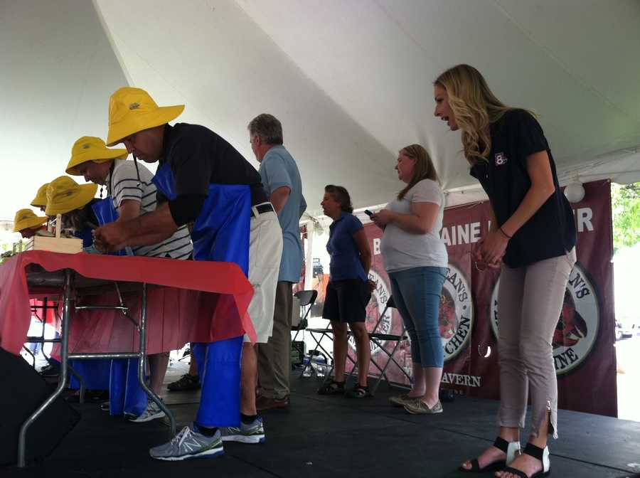 News 8's Norm Karkos going for shucking gold with Katie Thompson providing crucial encouragement.