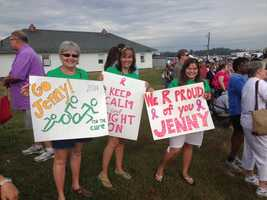 Spectators hold signs cheering on a competitor in Sunday's Tri for a Cure triathlon in South Portland.