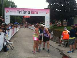 Racers embrace moments after they cross the finish line at the Tri for a Cure in South Portland on Sunday morning.