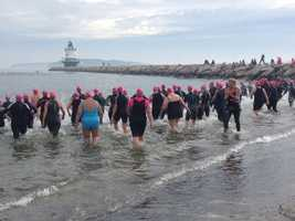 Competitors wade into the ocean in South Portland to begin a 1/3-mile swim as part of Sunday's Tri for a Cure.