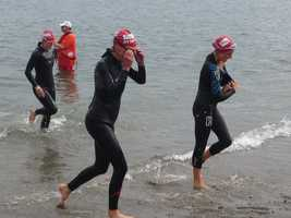 Competitors leave the water after finishing a 1/3-mile swim as part of Sunday's Tri for a Cure.