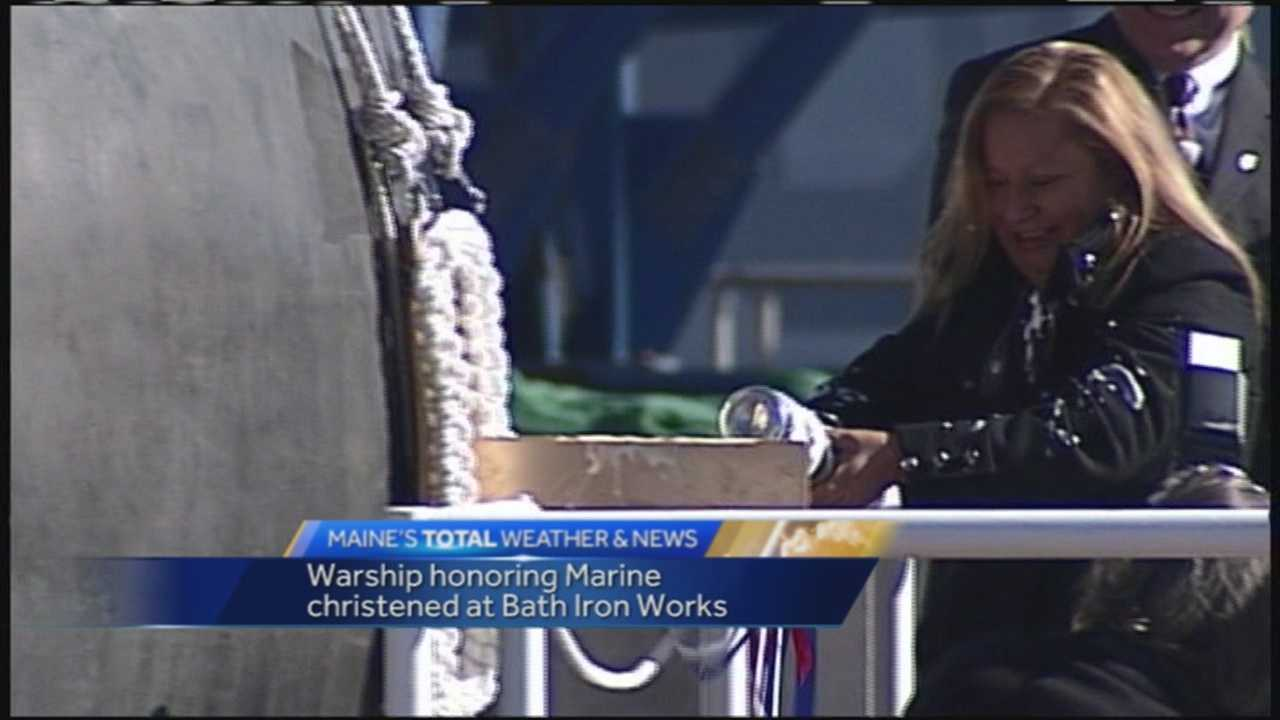 The mother of a Marine who was posthumously awarded the Navy Cross for shielding fellow Marines from a grenade has christened the ship bearing her son's name by crashing a bottle of Champagne on the ship's bow.
