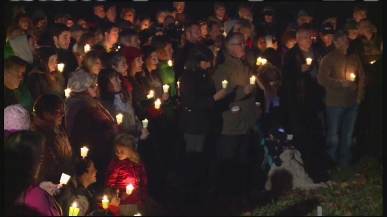 Candles lit up a cold November night as friends, family and neighbors gathered to mourn the deaths of the three victims of Wednesday's triple homicide.
