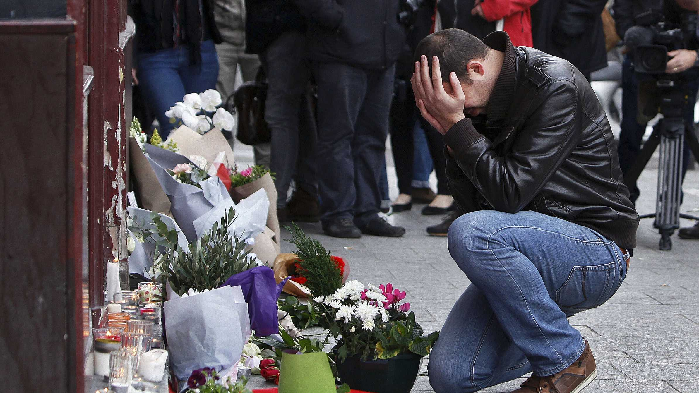 A man holds his head in his hands as he lays flowers in front of the Carillon cafe, in Paris, Saturday, Nov.14, 2015.
