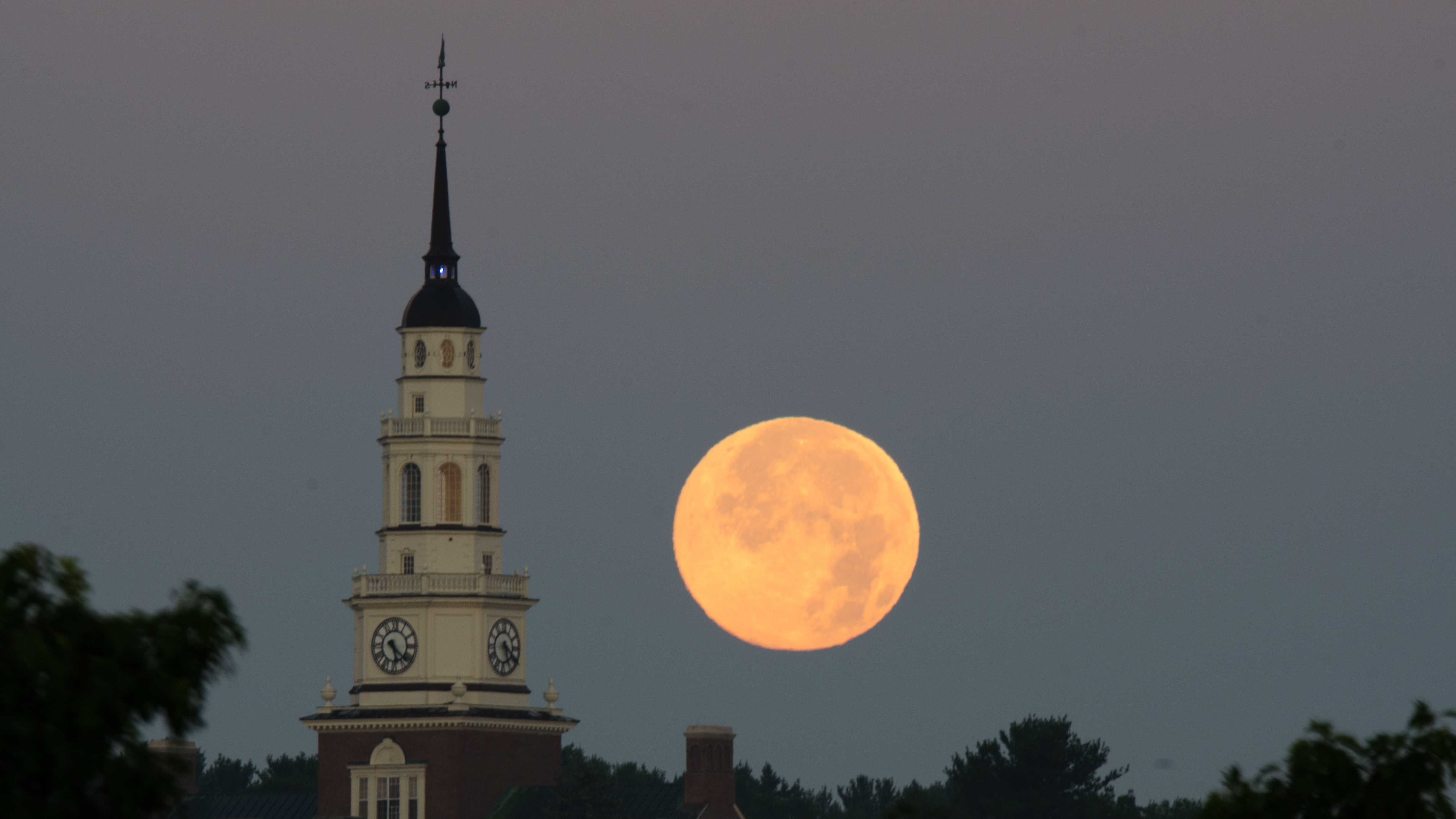 A full moon sets behind a steeple at Colby College.