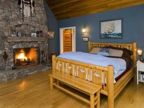 The master suite has a fireplace and his and her closets, with views of the sandy cove and lake.