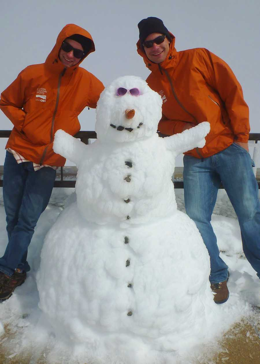 Workers build a snowman on Mt. Washington.
