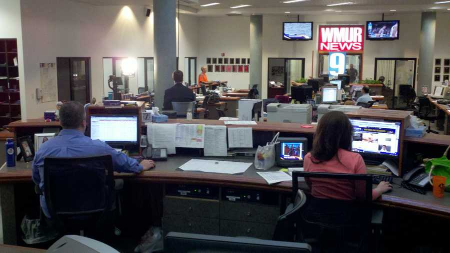 6:11 pm: 10 p.m. producer Keith Harrington and 11 p.m. producer Lisa Thalhamer work on their shows, while Jamie Staton goes live on-air in the background.