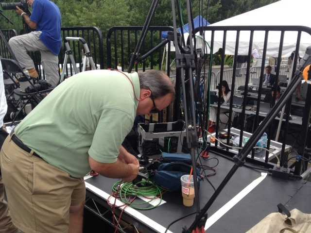 Photographer Danny Ryan prepares his camera and sound equipment at the Romney event.