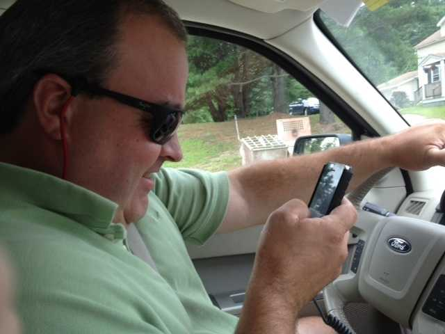 Photographer Danny Ryan checks his messages while stopped at a red light.