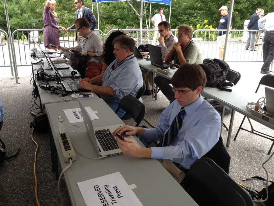 Reporters (and at least one intern) are set up at press tables at the Romney event.