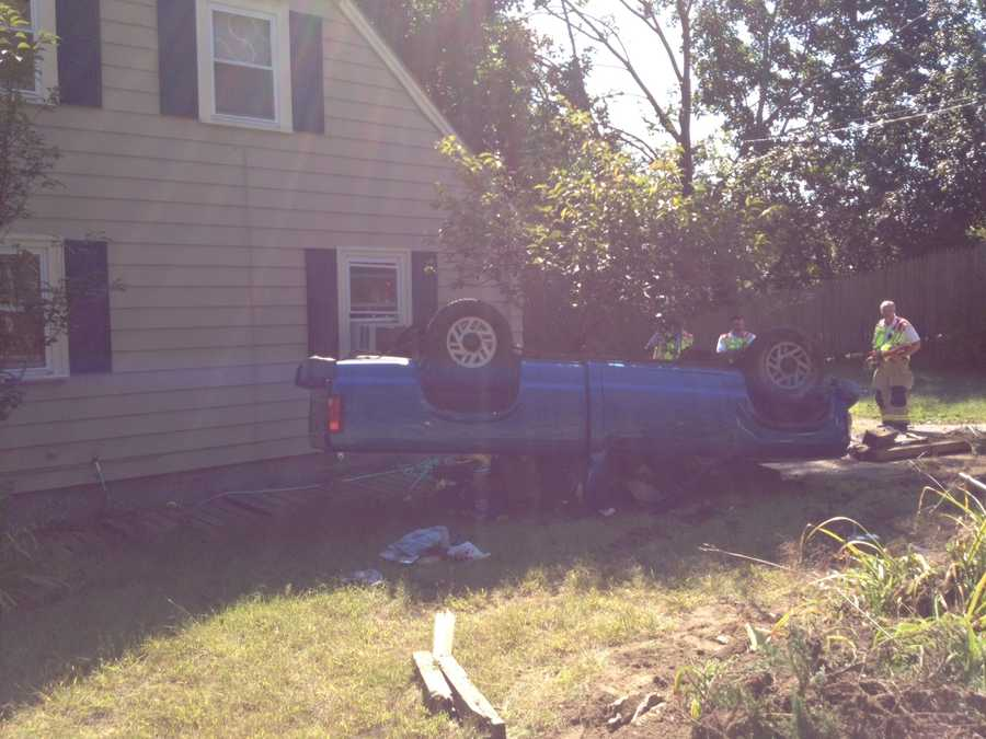 A pickup truck crosses the center line on Elm Street in Goffstown and ends up rolling over in the yard of a home.