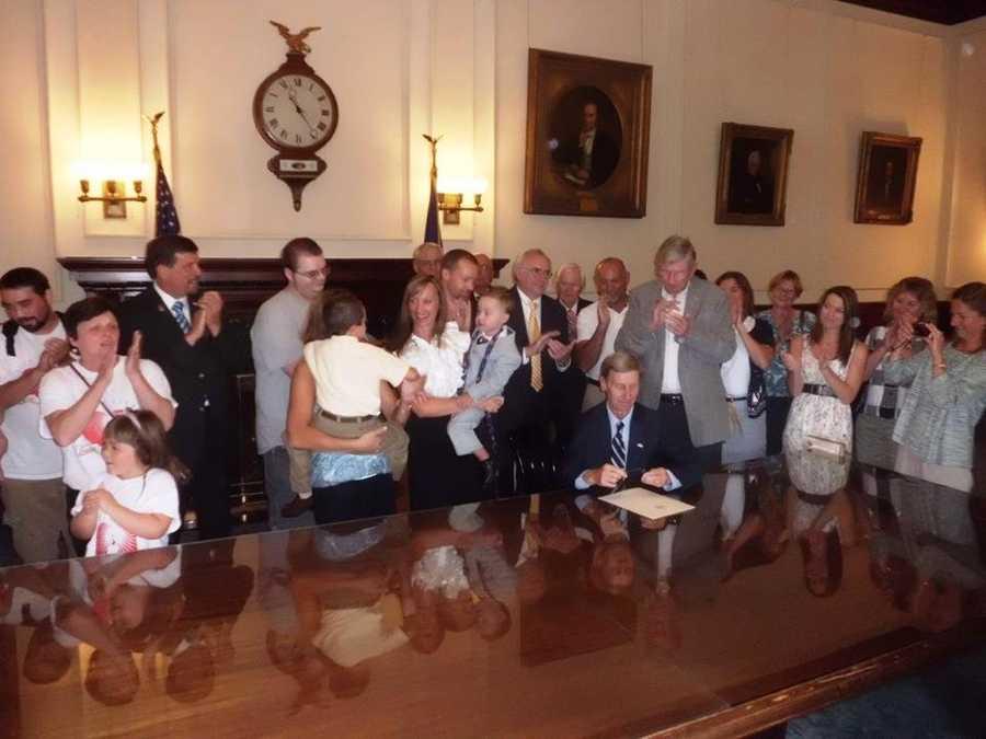 "Governor John Lynch signing Senate Bill 348, also known as ""Parker's Law."" Also pictured are bill sponsors Senator Jack Barnes, Senator John Reagan, the Bolton family, and advocates."