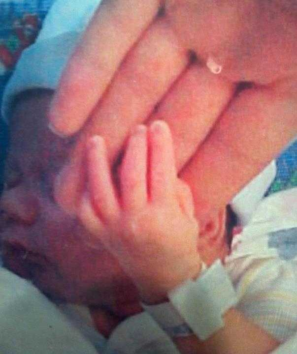 Baby Caleb at 3 pounds, 1 ounce touching his mom's hand.