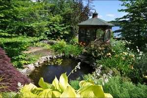 A gazebo by a waterfall provides an always cool place on hot summer days. Stone walkways, a white sugar sand beach, koi pond, running stream, and room for a tennis court are also features of this NH estate property.