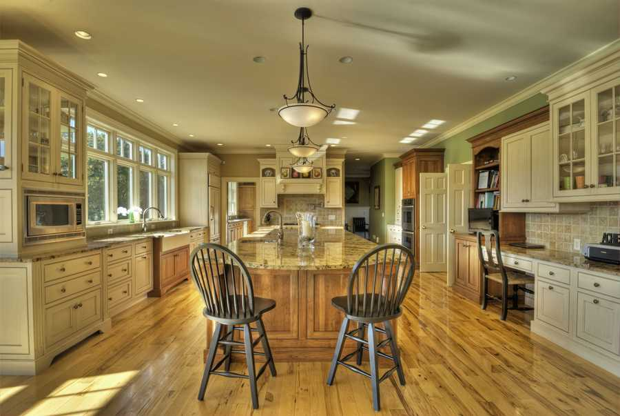 The 20 x 30 foot kitchen features a 13-foot island, a walk-in pantry and views of the property.