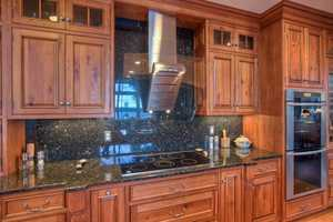 The high-end kitchen features custom distressed Cherry cabinets.
