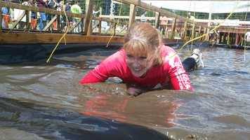 """Audrey tries to avoid the sting of the """"Electric Eel"""" -- an obstacle that shocks Mudders as they work their way on hands and knees through water."""