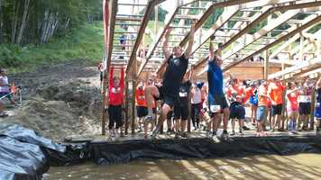 """This isn't your playground monkey bars -- the """"Funky Monkey"""" obstacle has Mudders climbing upwards over a pool of muddy water."""