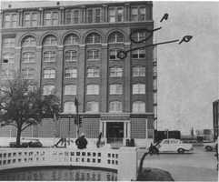 The photograph was taken on March 20, 1964, and marked by Howard Brennan during his testimony before the Warren Commission to show the window (A) in which he saw a man with a rifle, and the window (B) on the fifth floor in which he saw people watching the motorcade.