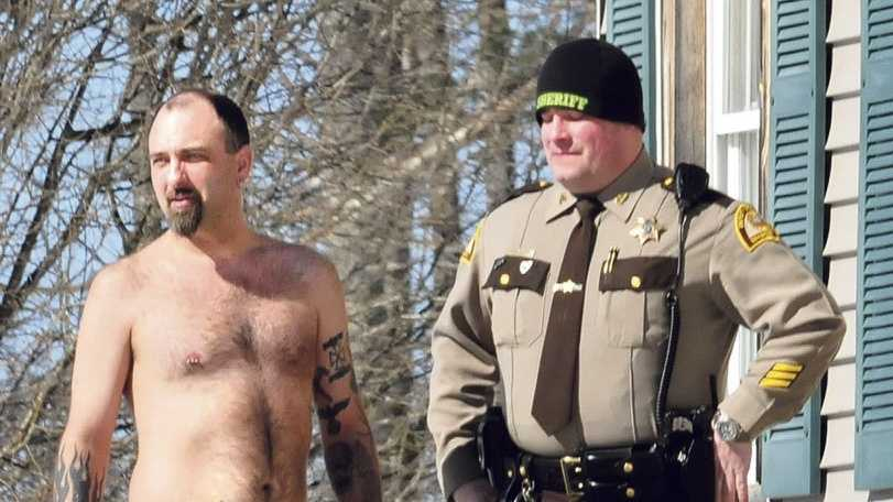 Norridgewock resident Michael Smith stands beside a Somerset County sheriff's deputy Tuesday morning. The tattoo of a pistol on his stomach was mistaken for a real firearm by employees of Lucas Tree Experts after, according to Smith, workers woke him up while they were cutting wood for Central Maine Power Co. The workers called police. Photo courtesy Morning Sentinel