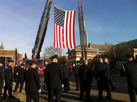 A flag honors firefighter Edward Walsh in Watertown Wednesday for his funeral.
