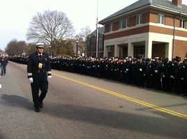 Firefighters stand at attention outside the Watertown Fire Department