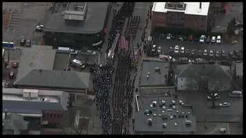This aerial photo shows the number of firefighters, police officers and people watching the procession for fallen Boston Fire Lt. Ed Walsh.