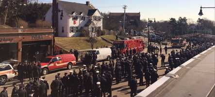 Firefighters gather on Centre Street in West Roxbury
