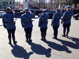 Massachusetts State Police troopers salute as the procession goes by.