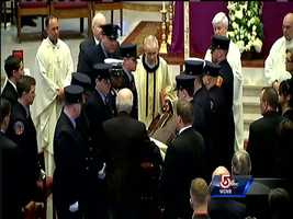 Members of the Boston Fire Department bring the casket with the body of Michael Kennedy into Holy Name Church in West Roxbury.