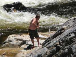 Below him, a man was fishing and catching one right in the falls.