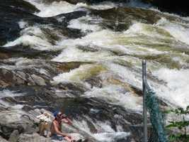 On the edge of the falls, a man sat with a backpack and he was drinking one can after another of some sort of beverage.