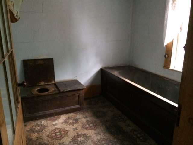 """This tin tub and """"one-holer"""" have been in the house since it was built."""