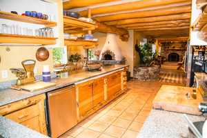 The kitchen includes granite counter tops and a wood-fired oven.