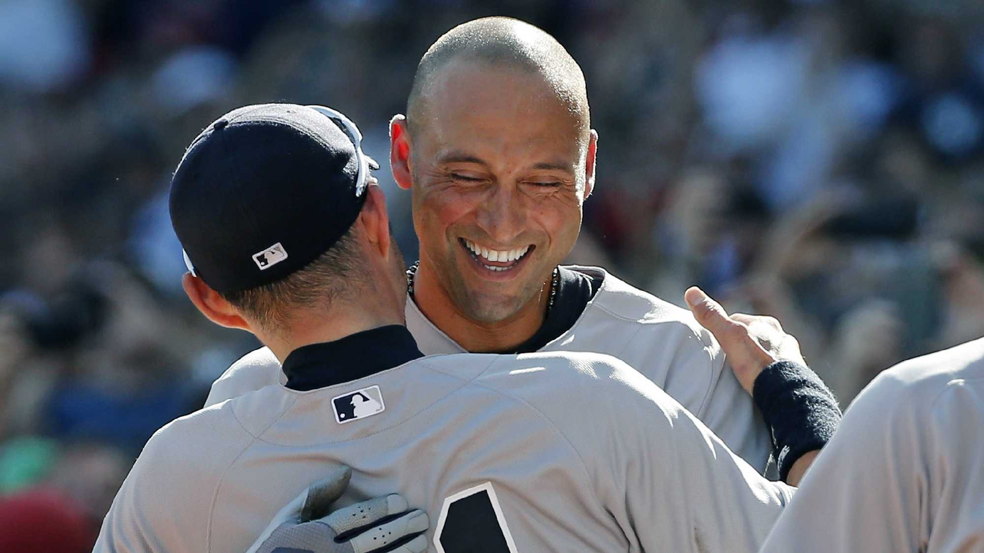 Jeter hugs teammate Ichiro Suzuki after coming out of the baseball game.