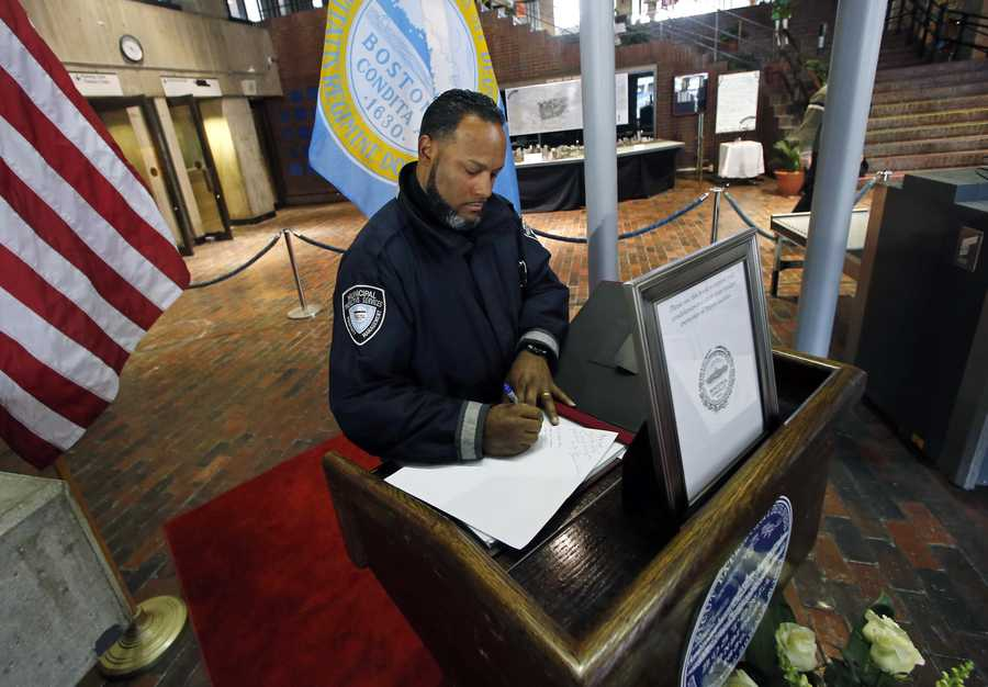 Roman Colon, an officer with Municipal Protective Services, signs a condolence book for former Boston Mayor Thomas Menino in the lobby of City Hall in Boston