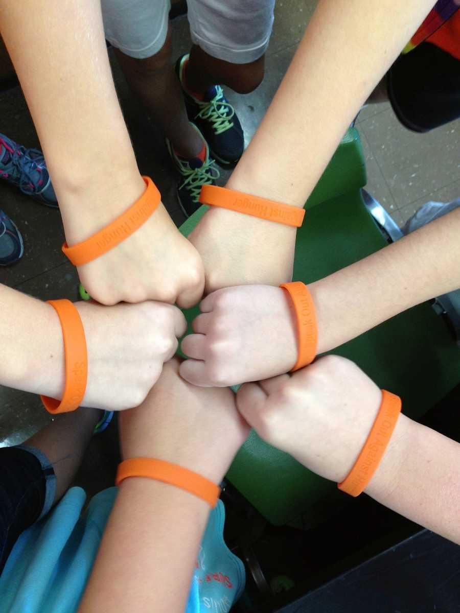 """Friends support Elsa and ending hunger by purchasing bracelets for """"Wear Orange Day"""" at school. 2013 (6th grade classmates)"""