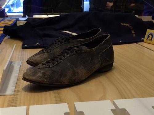 Early 20th century running shoes on display near finish line at Runbase