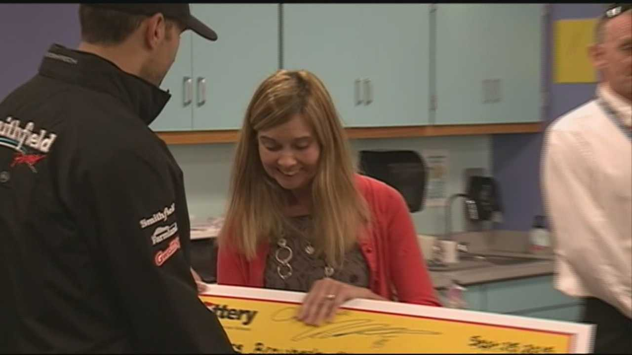 A teacher from Meredith won an essay contest hosted by the New Hampshire lottery. NASCAR driver Aric Almirola surprised her with the news and a check.