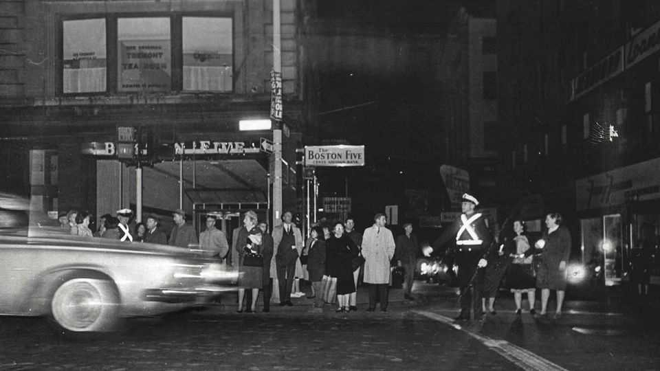 In this Nov. 9, 1965 photo, a police officer wearing a reflective belt directs pedestrians and regulates traffic on Tremont Street at rush hour during a power outage in Boston. The power failure, originating at a Canadian generating station near Niagara Falls, spread across the Northeast U.S., and parts of Canada, leaving 30 million people without power for hours.