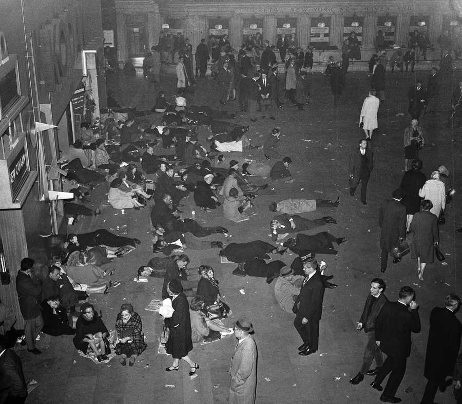 In this Nov. 9, 1965 file photo, people illuminated by emergency lighting sit, sleep and wander around in the main waiting room of New York's Grand Central Terminal during the massive power failure that plunged tens of millions into darkness across the northeastern U.S. and southern Canada 50 years ago. In New York City, it came at 5:27 p.m., the height of the evening commute, trapping hundreds of thousands of subway riders in their train cars, stranding others in building elevators, and turning Grand Central into an ad-hoc bedroom for commuters who couldn't get home.